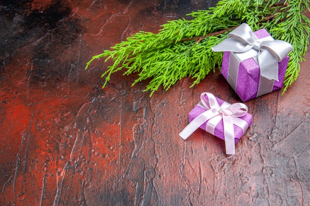 Top view xmas gifts with pink box and white ribbon tree branch on english red background