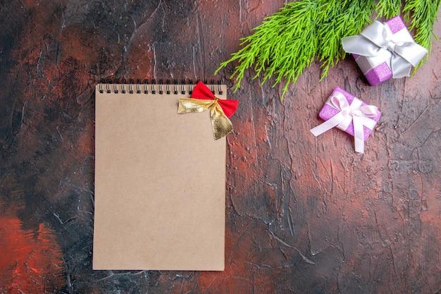 Regali di natale vista dall'alto con scatola rosa e nastro bianco ramo di un albero un quaderno su superficie rosso scuro