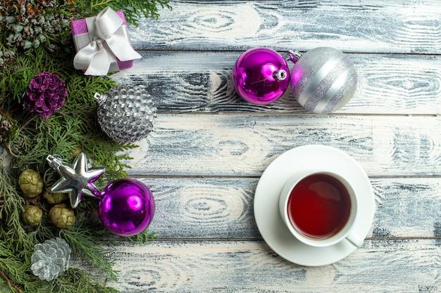 상위 뷰 크리스마스 장식품 작은 선물 전나무 나뭇가지 크리스마스 장난감 나무 표면에 차 한 잔