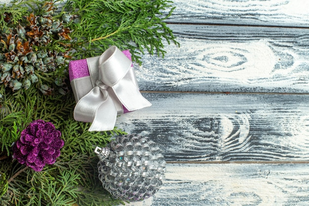 상위 뷰 크리스마스 장식품 나무 배경에 작은 선물 전나무 나뭇가지 크리스마스 장난감