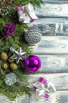 상위 뷰 크리스마스 장식품 나무 표면에 작은 선물 전나무 나뭇가지 크리스마스 장난감 무료 사진