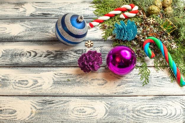 Вид сверху рождественские украшения подарки конфеты еловые ветки на деревянной поверхности