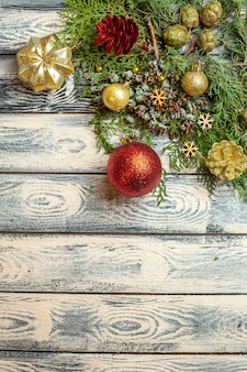 Top view xmas ornnaments gifts candies fir tree branches on wooden background free space
