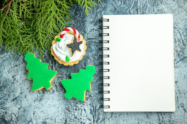 Top view xmas tart pine branch xmas tree biscuits notepad on grey table