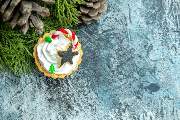 Top view xmas tart pine branches pinecones on grey table with free space