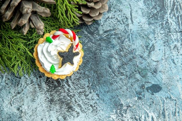 空きスペースのある灰色のテーブルの上のビュークリスマスタルト松枝松ぼっくり