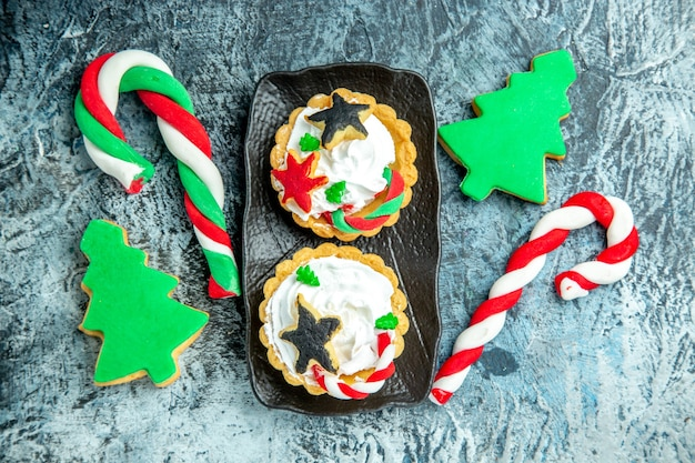 Вид сверху рождественские пироги на черной тарелке, рождественские конфеты, рождественское печенье на сером столе