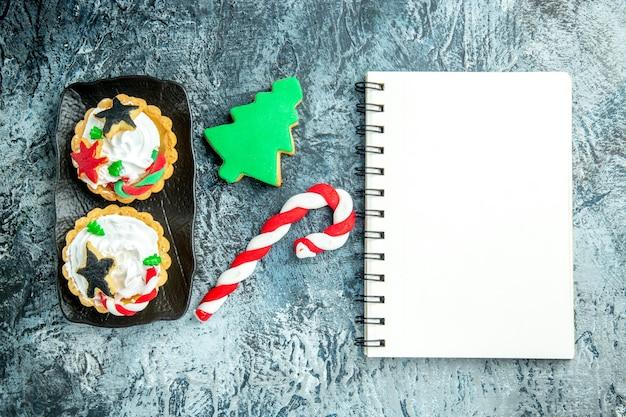 검정 잉크 판에 상위 뷰 크리스마스 타르트 회색 테이블에 크리스마스 사탕과 크리스마스 트리 비스킷 메모장