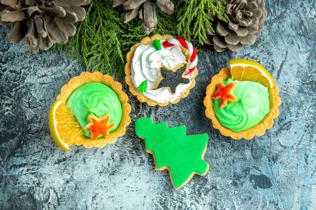 Вид сверху рождественские пироги сосновые ветки шишки на сером столе