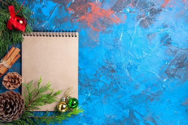 Sfere dell'albero di natale di vista superiore su una pigna dei rami di albero di pino del taccuino sullo spazio libero di superficie blu