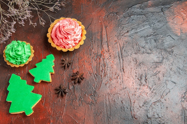 Top view of xmas tree biscuits different sizes tarts anises on dark red surface