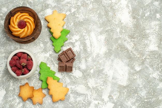 Biscotto dei biscotti dell'albero di natale di vista superiore nella ciotola della ciotola con il cioccolato dei lamponi sullo spazio libero della tavola grigia