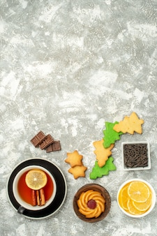Vista dall'alto albero di natale biscotti tazza di ciotole di tè con fette di cioccolato e limone sullo spazio della copia tavolo grigio