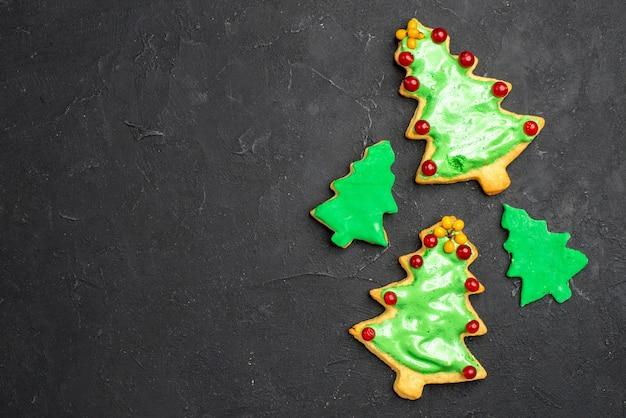 暗い孤立した表面の空き領域にトップビューのクリスマスツリークッキー