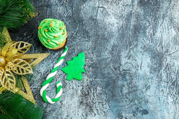 Vista dall'alto albero di natale cupcake natale caramelle ornamenti di natale su superficie grigia
