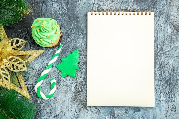 Vista dall'alto albero di natale cupcake caramelle di natale ornamenti di natale un quaderno su superficie grigia