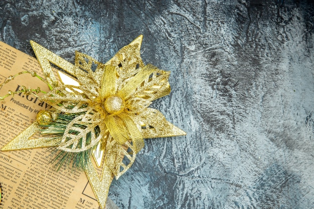 Top view xmas tree ornament on newspaper on dark surface