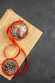 Top view xmas tree toy in ribbon on newspaper on dark surface