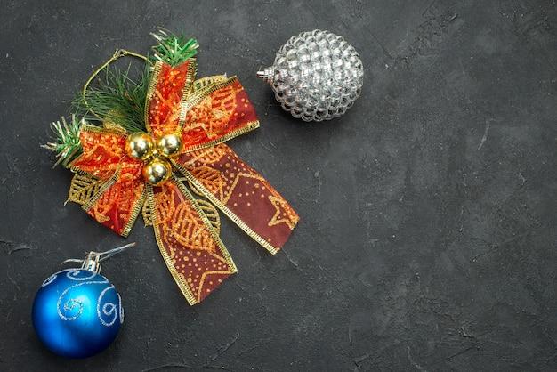 暗い背景の空き領域にクリスマスチュールの弓とクリスマスツリーのボールのおもちゃの上面図