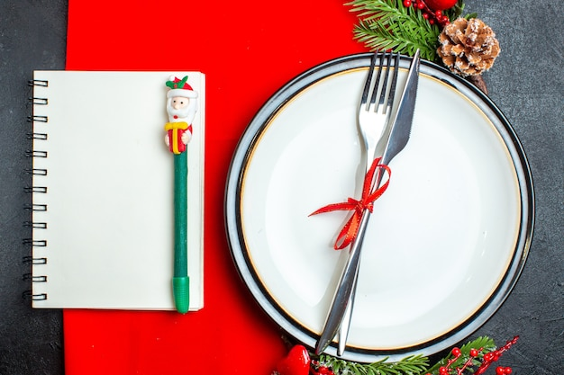 Top view of xsmas background with cutlery set with red ribbon on a dinner plate decoration accessories fir branches next to notebook with pen on a red napkin
