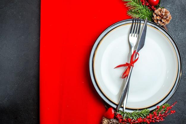 Vista dall'alto dello sfondo di natale con posate con nastro su un piatto da pranzo accessori per la decorazione rami di abete su un tovagliolo rosso sul lato sinistro su uno sfondo scuro