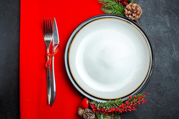 Vista dall'alto dello sfondo di natale con accessori per la decorazione del piatto da pranzo rami di abete e posate su un tovagliolo rosso