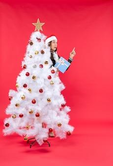 Vista dall'alto dell'umore natalizio con la ragazza sorpresa in un abito nero con il cappello di babbo natale