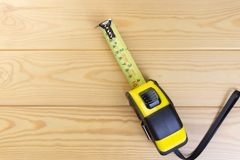 Top View Yellow and Black Measuring Tape on Wooden Floor Space for text