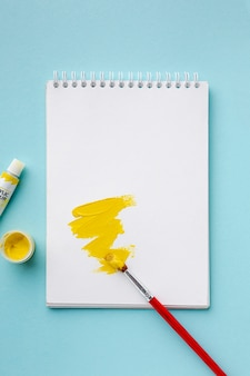 Top view of yellow aquarelle on notebook