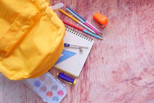 Top view of yellow backpack with different colorful stationery on table.