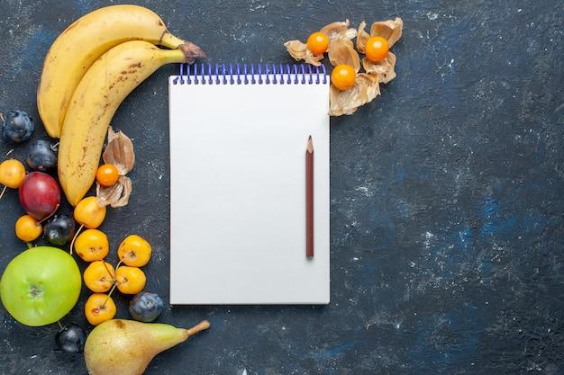 Vista dall'alto di banane gialle matita blocco note con mele verdi fresche pere prugne e ciliegie dolci sulla scrivania scura vitamina frutta bacca salute