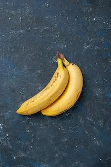 暗いテーブルフルーツの上のビュー黄色のバナナのペアの果実