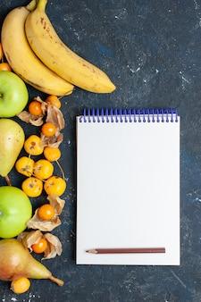上面図黄色いバナナのペアと新鮮な青リンゴ梨のメモ帳と紺色の机の上の甘いサクランボフルーツベリー新鮮な健康ビタミン