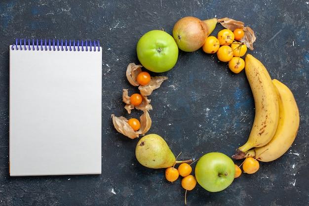 上面図黄色いバナナと新鮮な青リンゴ梨甘いサクランボのメモ帳ダークブルーのデスクフルーツベリー新鮮な健康ビタミン
