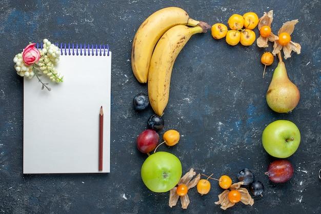 Vista dall'alto di banane gialle con fresche mele verdi blocco note pere prugne e ciliegie dolci sulla scrivania scura vitamina frutta bacca salute