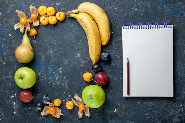 ダークデスクのフルーツベリーの健康に新鮮な青リンゴ梨プラムと甘いサクランボのメモ帳と上面図黄色のバナナ