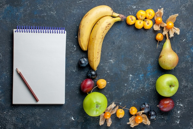 Вид сверху желтые бананы со свежими зелеными яблоками, груши, сливы, блокнот и черешня на темном столе, витамин, фрукты, ягоды, здоровье