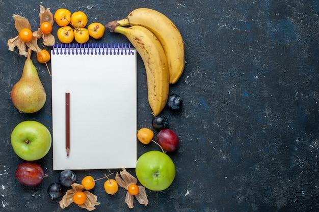 Vista dall'alto di banane gialle con fresche mele verdi pere prugne blocco note matita e ciliegie dolci sulla scrivania blu scuro vitamina salute frutti di bosco