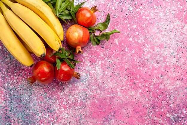 Вид сверху желтые бананы с гранатами на розовой поверхности