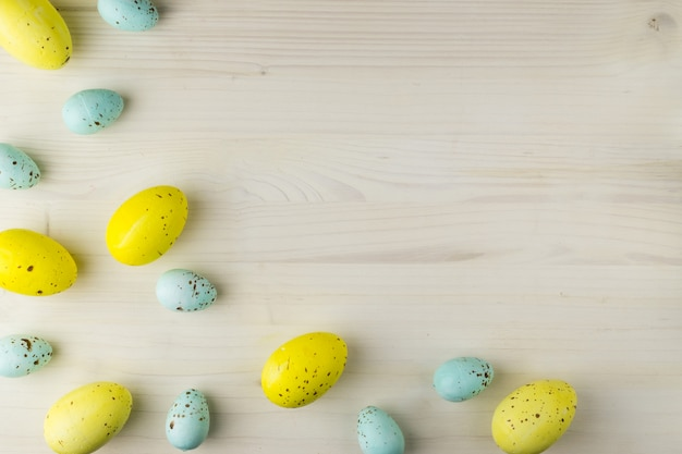 Top view of a yellow and blue easter eggs on light wood background with message space.