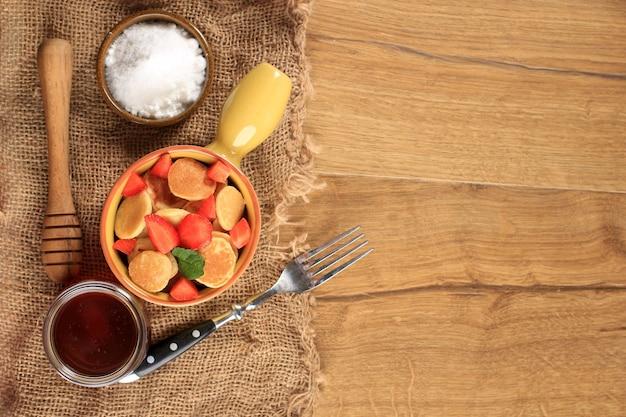 Вид сверху желтая миска с ручкой, полная крошечных блинов или популярная как вирусная закуска из зерновых блинов