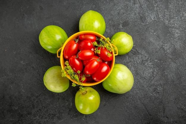 상위 뷰 노란색 양동이 체리 토마토와 딜 꽃으로 가득하고 복사 공간이 어두운 땅에 녹색 토마토로 반올림
