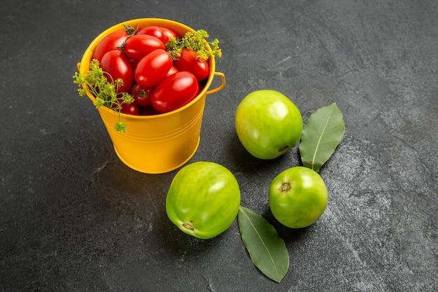 Vista dall'alto secchio giallo riempito con pomodorini e fiori di aneto foglie di alloro e pomodori verdi su fondo scuro con spazio di copia