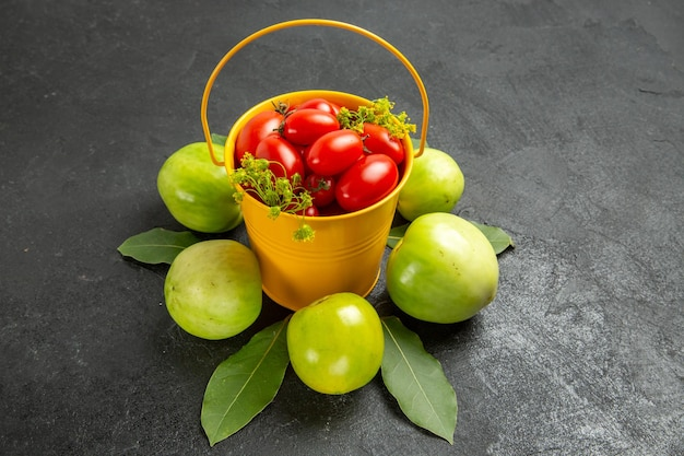 Top view yellow bucket filled with cherry tomatoes and dill flowers surrounded with green tomatoes and bay leaves on dark ground with free space