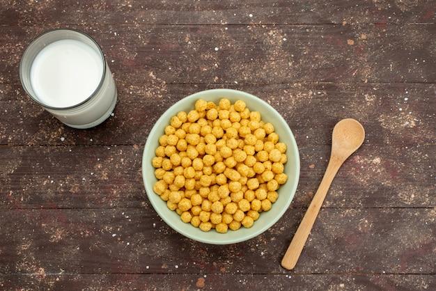 Vista superiore cereali gialli all'interno della piastra con latte freddo fresco e cucchiaio su scuro, colazione cereali cereali