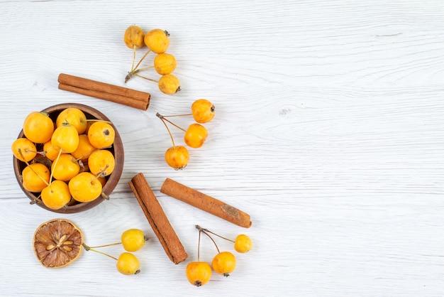 トップビュー黄色のサクランボは、明るい背景のフルーツの新鮮なカラー写真にシナモンと一緒にまろやかで新鮮です