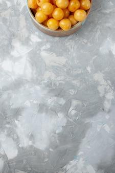 Вид сверху желтые вишни спелые спелые внутри тарелки на сером столе фрукты свежие спелые летние спелые