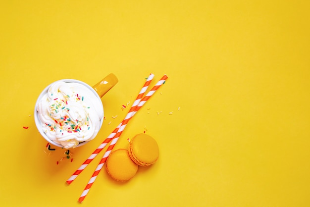 Top view of yellow coffee cup, straws and french macaroons on yellow