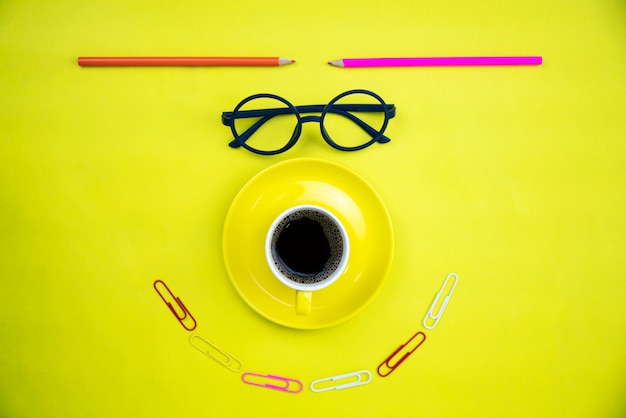 Top view of yellow coffee cup with teacher glasses and colorful pencil