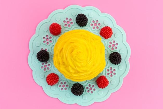 Una torta cremosa gialla di vista superiore con i frutti di bosco freschi sul colore della torta del biscotto dei frutti di bosco e blu e rosa